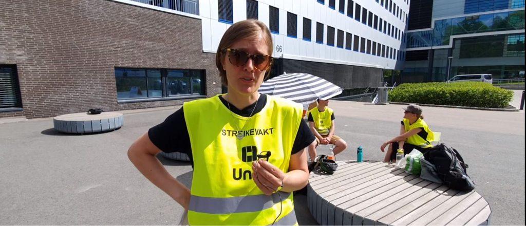 Kvinne i Unio-streikevest foran sittende streikevakt og en stor offentlig bygning