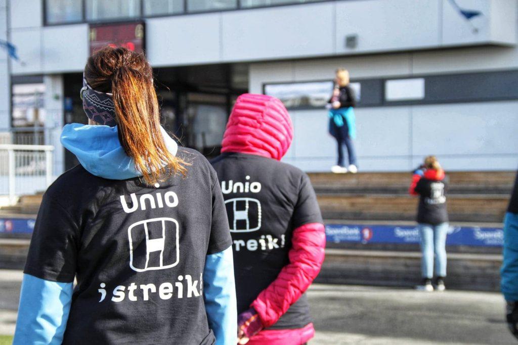 """Foto: Person står med ryggen til med T-skjorte med teksten """"Unio i streik"""". I bakgrunnen holder en person en appell."""